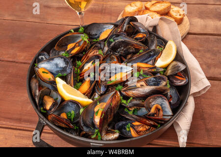 Marinara mussels, moules mariniere, with toasted bread, lemon slices, and wine on a dark rustic wooden background - Stock Photo