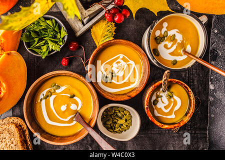 Autumn pumpkin soup puree with cream in cups, the autumn scenery. Healthy vegan food concept. Autumn food concept.