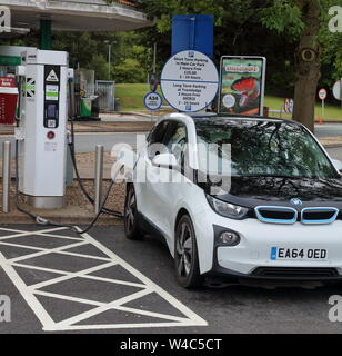 Filling up the car at a motorway services with eco friendly electricity with quick charging and treating the environment with respect. - Stock Photo