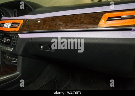Close-up on a car panel with a wooden finish with paper tape glued around the perimeter for polishing and removing scratches from the surface. Auto se - Stock Photo