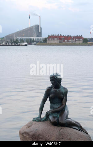 The Little Mermaid in the city of Copenhagen. Some industries in the background. - Stock Photo