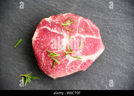 Raw pork meat / Fresh steak ready for grill with spices rosemary on black background - Stock Photo