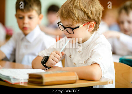 Little first-grader, girl-student goes to school on knowledge day - September First. Student of elementary school in uniform with bows posing in class - Stock Photo