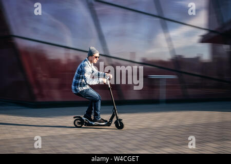 Young man in casual wear on electric kick scooter on city street in motion blur against modern glass office building - Stock Photo