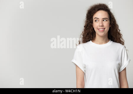 Attractive young woman standing aside looking at copyspace grey background - Stock Photo