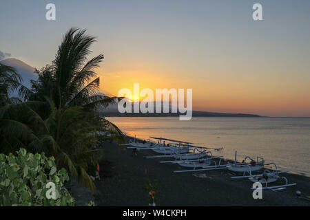 The sun set behind a mountain range near the active volcano on Bali Island. The sky stained orange from the rising sun. Calm sea level colored. - Stock Photo