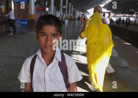A young schoolboy in Mumbai, India, waiting or his local train at Chhatrapati Shivaji Maharaj Terminus, the city's busiest railway station