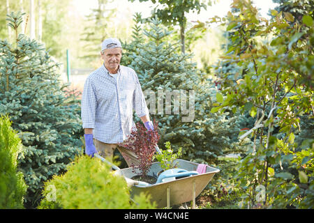 Portrait of mature man pulling cart while working in garden outdoors, copy space - Stock Photo