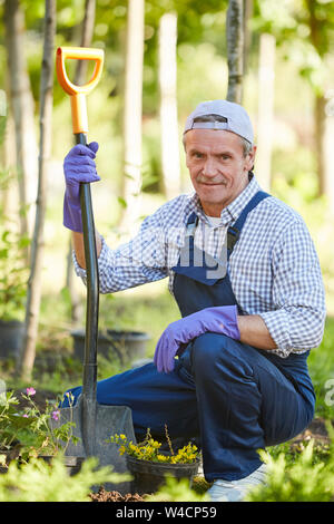 Full length portrait of mature man working in garden and looking at camera - Stock Photo