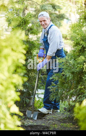 Full length portrait of smiling mature man working in garden and looking at camera - Stock Photo