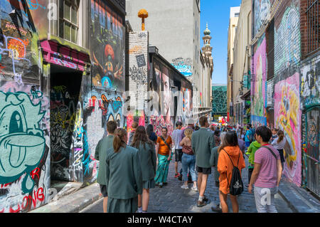 Tourists viewing street art on Hosier Lane in the Central Business District, Melbourne, Victoria, Australia - Stock Photo