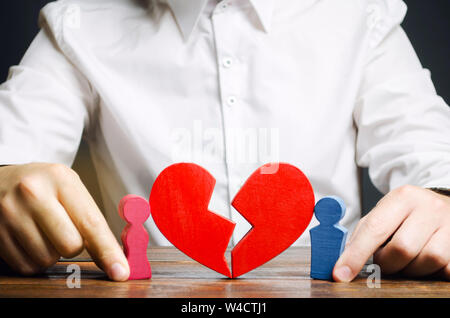 Family psychologist collects the red heart near a couple lovers. Renewal of the relationship. Family psychotherapist services. Reconciliation. Search - Stock Photo