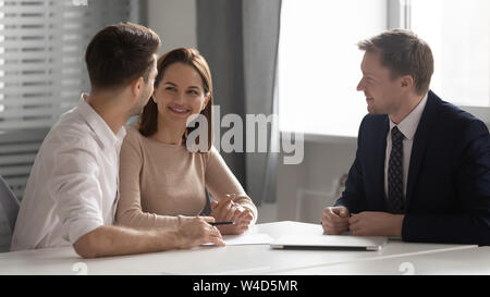 Happy young family couple making decision meeting bank manager insurer - Stock Photo