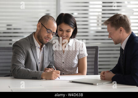 Happy mixed ethnicity young couple customers sign loan investment contract - Stock Photo
