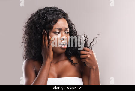 Sad african woman looking at dry edges of damaged hair - Stock Photo