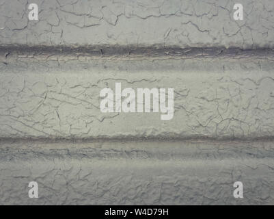 Grey paint peeling off a metallic surface background. Old grungy, weathered painted wall texture. Cracked, dirty, silver plaster falling off the const - Stock Photo