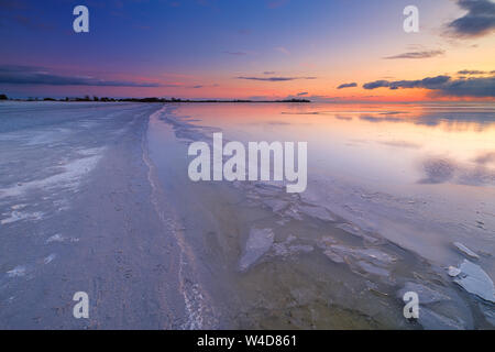 A frozen lake on a cold winters evening at the beach with ice on the foreground - Lake IJsselmeer, The Netherlands - Stock Photo