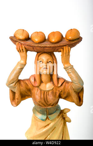 Christmas nativity figure depicting life in olden times in Naples Italy EU and showing a young woman delivering freshly baked bread on a cane tray bal - Stock Photo