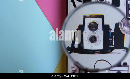 Photography concept. Picture of Vintage camera with flash on notebook zoomed in with magnifying glass. Color abstract background - Stock Photo