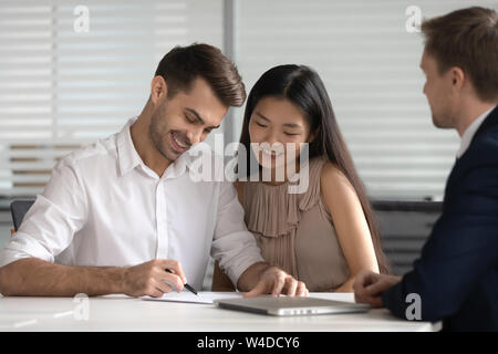 Happy mixed ethnicity couple customers sign mortgage investment loan contract - Stock Photo