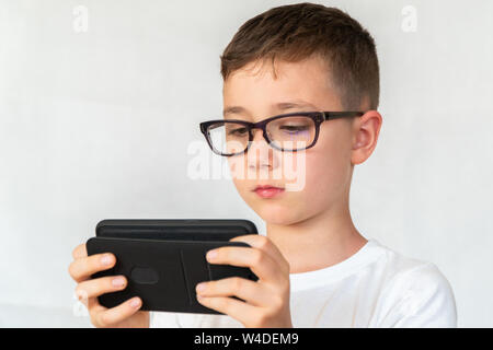 School boy looks handsome smartphone video, in glasses, dressed in white shirt, on white background, screams in fright - Stock Photo