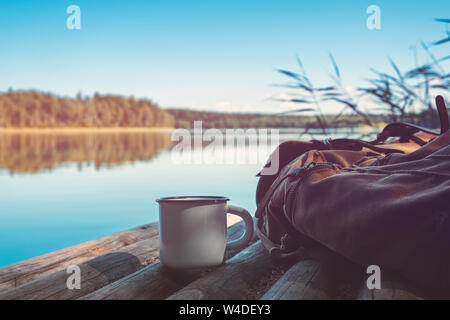 Enameled cup of coffee or tea, backpack of traveller on wooden pier on summer tranquil lake. - Stock Photo