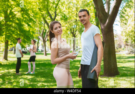 Attractive young couple posing to camera after training outdoors - Stock Photo