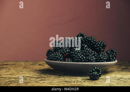 Fresh blackberry in bowl on a old oak wooden table and dark-red wall background. - Stock Photo