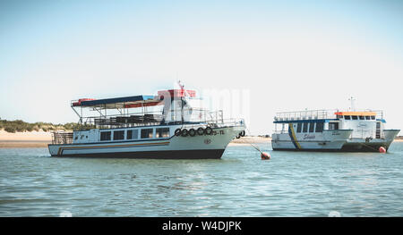 Tavira, Portugal - May 3, 2018: Tourist transport boats moored in the lagoons of the Ria Formosa Natural Park near the port of Tavira on a spring day - Stock Photo