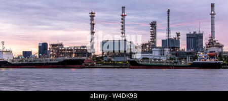 Banner of petroleum oil refinery plant beside river in twilight time. Crude Oil Process machinery - Stock Photo