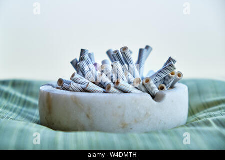 Ashtray filled with slim cigarette butts, laid on a soft pillow. Concept for quitting smoking, no tobacco day, quitting addiction, anti-smoking campai - Stock Photo