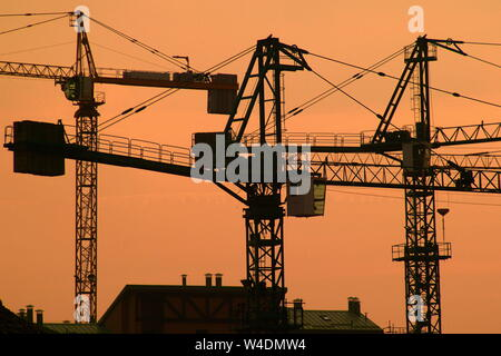 silhouette of construction crane on the background of orange sunset - Stock Photo