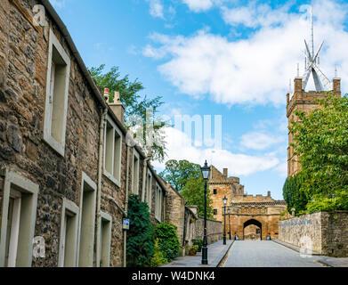 Cobbled narrow lane entrance, Linlithgow Palace, with St Michael's Parish Church, West Lothian, Scotland, UK - Stock Photo