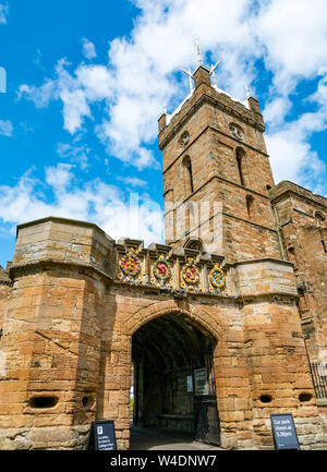 Gate entrance, Linlithgow Palace, Linlithgow, with St Michael's Parish Church tower, Scotland, UK - Stock Photo