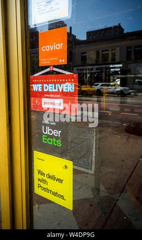 A restaurant in New York advertises its use of multiple delivery partners, seen on Saturday, July 20, 2019.  (© Richard B. Levine) - Stock Photo