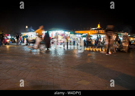 Night  market in Marrakech Jema el Fna Evening gathering of locals and tourists at traditional bustling Islamic low light market square in Morocco - Stock Photo