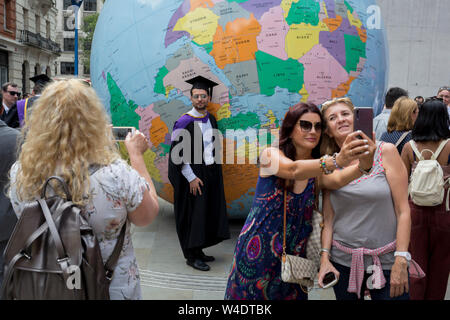 Beneath the sculpture by Turner Prize-winning artist Mark Wallinger entitled 'The World Turned Upside Down', new graduates straight after their graduation ceremonies meet family and friends outside the London School of Economics (LSE), on 22nd July 2019, in London, England. 'The World Turned Upside Down' is a large political globe, four metres in diameter, with nation states and borders outlined but with the simple and revolutionary twist of being inverted. Most of the landmasses now lie in the 'bottom' hemisphere with the countries and cities re-labelled for this new orientation. - Stock Photo