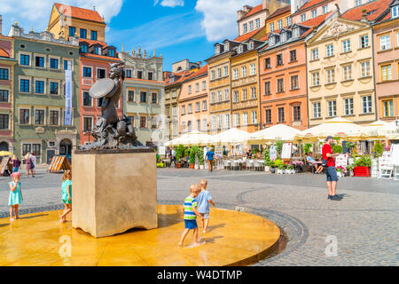 WARSAW, POLAND - JULY 19, 2019: Visitors enjoy summer day in the Warsaw Old Town Square, a busy square lined with burgher houses and upscale Polish ea - Stock Photo