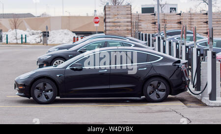 Tesla Model 3 parked plugged-in at a Tesla Supercharger with other vehicles at CF Sherway Gardens, Toronto (Etobicoke). - Stock Photo
