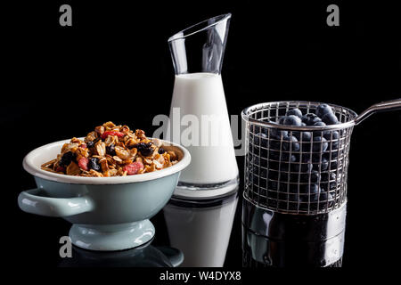 Blueberries in steel cup stainer, granola in an enamel white and blue bowl and yogurt in a glass jug on black background from side - Stock Photo
