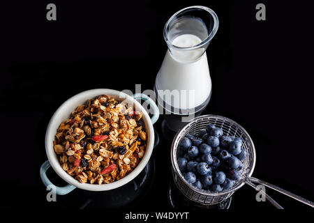 Blueberries in steel cup stainer, granola in an enamel white and blue bowl and yogurt in a glass jug on black background directly from above - Stock Photo