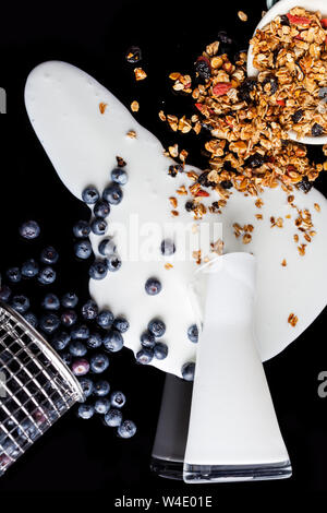 Yogurt spilled from glass pitcher, blueberries poured from steel stainer and granola poured and scattered from enamel bowl mixed together in a mess on - Stock Photo