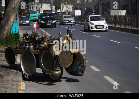 Istanbul, Turkey - April 5, 2018 : There are many antique metal objects on a wheelbarrow at road with vehicles. Like trays, bowls and pitchers. - Stock Photo