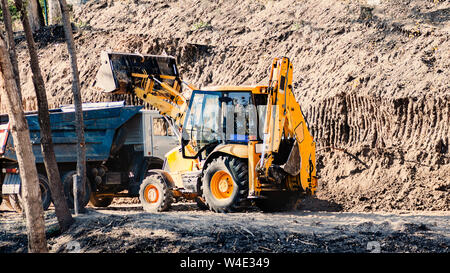 dump trucks and tractor are working to adjust the soil surface in the construction area amid the hot weather during the daytime of the summer. - Stock Photo
