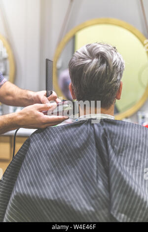 Barber styling hair of his client in front of mirror by using comb and clipper at barbershop. - Stock Photo