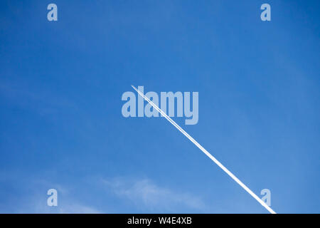 Looking above into the beautiful bright blue sky, with an aeroplane flying high leaving contrails behind in its path - Stock Photo