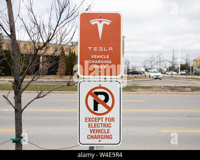 Tesla Vehicle Charging Only Sign and No Parking Except For Electric Vehicle Charging Sign at Vaughan Mills Tesla Supercharger Location. - Stock Photo