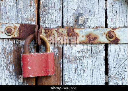 Old brown padlock on a gray door with wooden planks of cracked paint and rust. Vintage gates with metal stripes and bolts