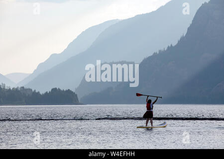Young girl stand-up paddleboarding on Upper Campbell Lake at Strathcona Park Lodge in Strathcona Provincial Park, near Campbell River, Vancouver Islan - Stock Photo