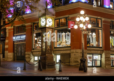 World-famous Gastown Steam Clock on Water St. and Cambie St. in downtown Vancouver, BC glowing at night. - Stock Photo